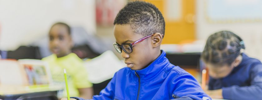 African boy in classroom writing